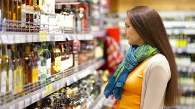 stock-footage-smiling-young-woman-choosing-a-bottle-of-red-wine