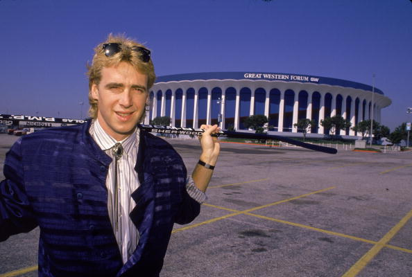 Portrait of Canadian hockey player Bernie Nicholls of the LA Kings as he stands in the parking lot of the Great Western Forum, Los Angeles, California, October 1989. He is dressed in a horizontally striped, collarless blue suit and balances a hockey stick across his shoulders. (Photo by Bruce Bennett Studios/Getty Images)